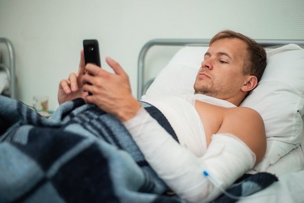 Bandaged patient lying on the bed in the hospital with a smartphone in his hands