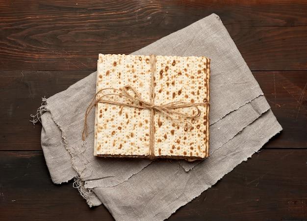 Bandaged stack of baked square matzoh on a gray napkin