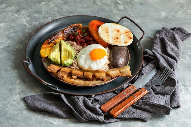Колумбийская еда. bandeja paisa, типичное блюдо в регионе антиокия в колумбии - чичаррон (жареная свиная грудинка), черный пудинг, колбаса, арепа, фасоль, жареный подорожник