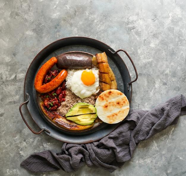 Колумбийская еда. bandeja paisa, типичное блюдо в регионе антиокия в колумбии - чичаррон (жареная свиная грудинка), черный пудинг, колбаса, арепа, фасоль, жареный подорожник, яйцо авокадо и рис.
