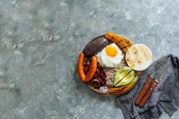 Колумбийская еда. bandeja paisa, типичное блюдо в регионе антиокия в колумбии - жареная свиная грудинка, черный пудинг, колбаса, арепа, фасоль, жареный подорожник, яйцо авокадо и рис.