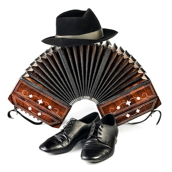 Bandoneon, tango shoes and a black hat isolated on white