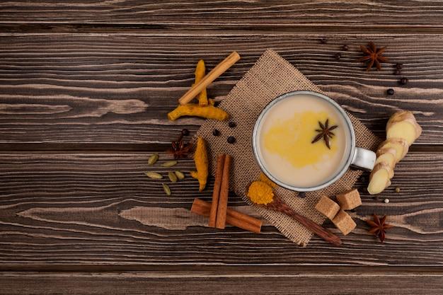 Bandrekは伝統的なインドネシアのジンジャーティーです。この飲み物はジャワ島で人気があります。ココナッツミルクとさまざまなスパイスから作られています。上面図、木製のテーブル。