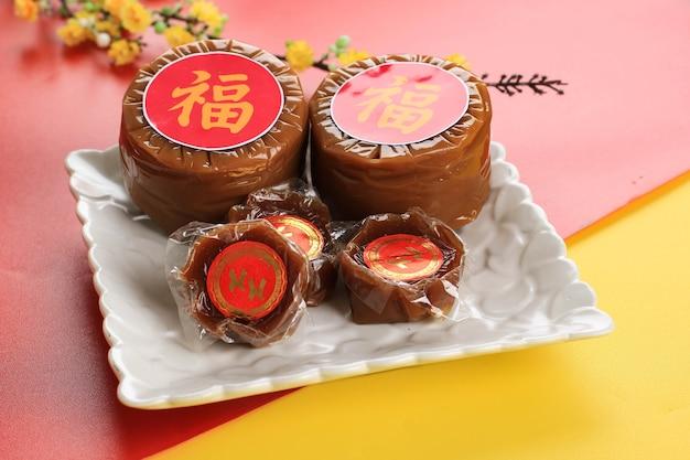 Бандунг, индонезия, 01012021: куэ керанджанг или ниан гао на белой тарелке. празднование китайского нового года в трех няньгао