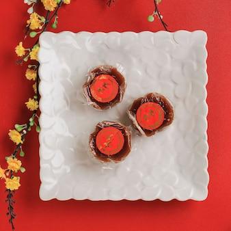 Бандунг, индонезия, 01012021: вид сверху куэ керанджанг или ниан гао на белой тарелке. три niangao mini для празднования китайского нового года