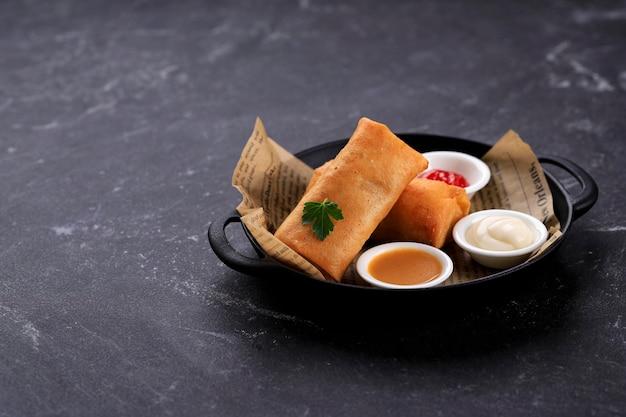 Бандунг, индонезия, 02122020: жареные во фритюре спринг-роллы, популярные как lumpia или popia. подается на серой сковороде, стол из черного мрамора. копировать пространство для текста