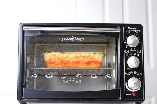 インドネシア、バンドン、10292020:ベーキングプロセス、スパゲッティブリュレの製造、キッチンのオーブン内の透明なベーキングディッシュ