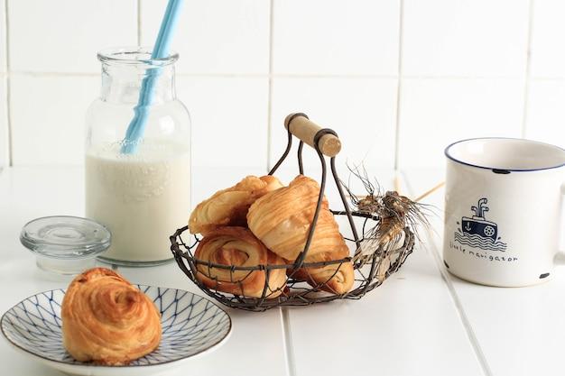 반둥, 인도네시아, 11102020: 우유를 곁들인 미니 크루아상, 프랑스산 버터를 곁들인 얇은 페이스트리. 화이트 주방에 접시와 짠 와이어 바구니에 제공.