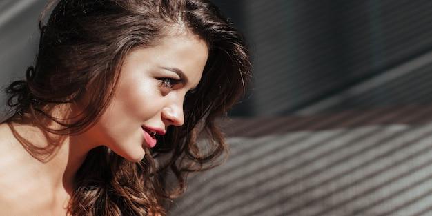 美しいメイクと豪華なセクシーな唇を持つブルネットの魅惑的な顔のバナークローズアップ