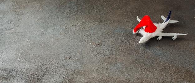 クリスマスや新年の旅行の概念。おもちゃの飛行機とサンタクロースの帽子。クリスマス旅行baner。