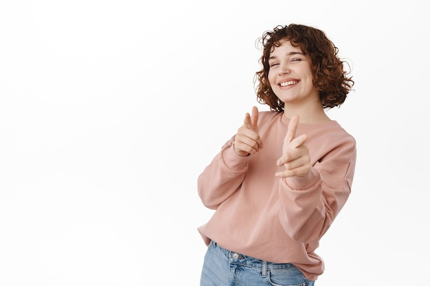뱅뱅 어떡해. 웃고 있는 쾌활한 소녀가 카메라를 향해 손가락 권총을 가리키고, 카메라를 보고 행복한 윙크를 하고, 당신을 초대하고, 좋은 일을 칭찬하고, 흰색 위에 서 있습니다.