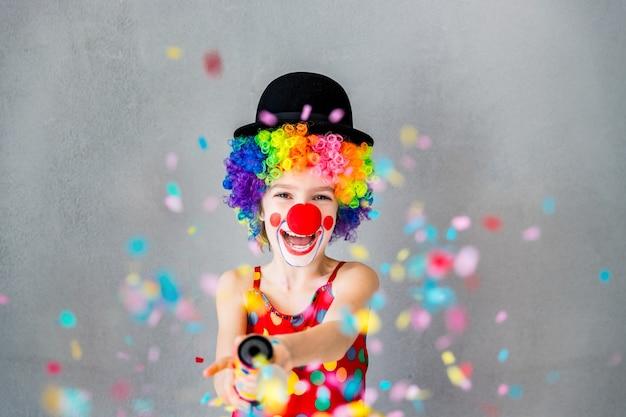 Хлопнуть! забавный клоун ребенка, играющий дома. конфетти поппер партии съемки ребенка. концепция 1 апреля дурака