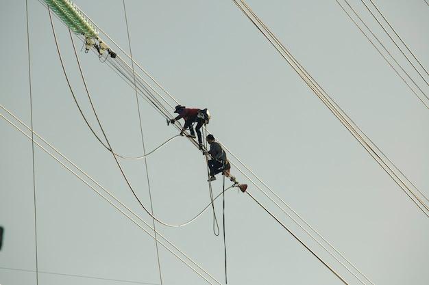 バンパコン発電所、タイ-2019年12月7日:ライン電気を歩く男性高電圧電柱の設置は、高所での作業を危険にさらし、安全な全身ハーネスを着用します。