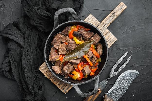 Тушеная говядина bangin подается в чугунной сковороде, на черном каменном фоне, плоская планировка, вид сверху, с местом для текста