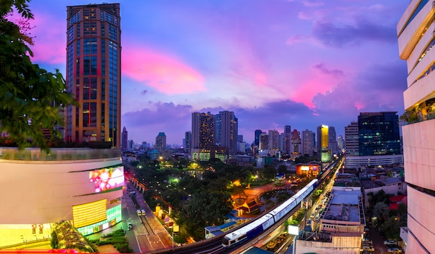 夕暮れに沿って前景に空の列車があるバンコクのビジネス地区。