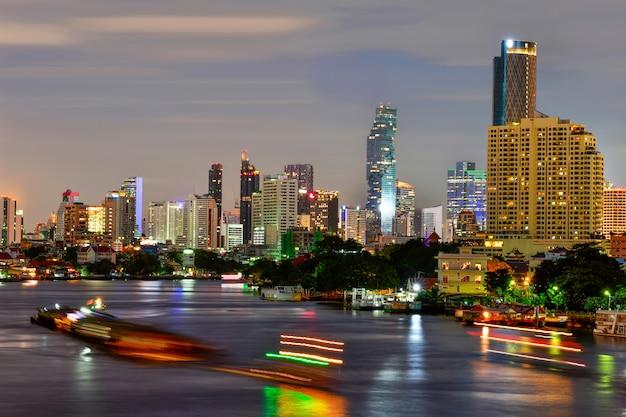 バンコク市の近代的なオフィスビル、マンション、タイの首都の夕焼け空の中にチャオプラヤー川のあるホテル