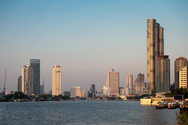 Bangkok city with sunshine on highrise buildings in downtown on chao phraya