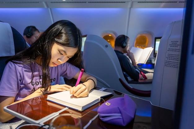 방콕, 태국 - 2015년 4월 4일 - 한 아시아 십대가 비행기를 타고 여행하는 동안 노트북에 글을 씁니다.