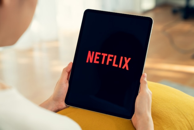 Bangkok, thailand - april 07, 2020 : women use netflix app on ipad pro screen. netflix is an international leading subscription service for watching tv episodes and movies.
