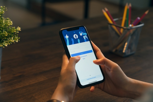 Bangkok, thailand - april 13, 2020 : hand is holding phone and the facebook screen on apple iphone, social media are using for information sharing and networking.