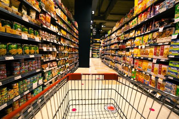 バンコクタイ-2020年4月女性と子供たちの焦点がぼけたぼやけスーパーマーケットのスーパーマーケットで飲み物の棚に置かれた食料品購入の買いだめ