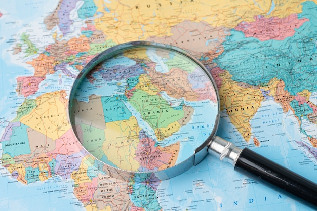 Bangkok, thailand - august 01, 2020  saudi arabia, asia, magnifying glass close up with colorful world map