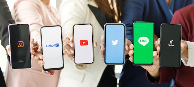 Bangkok/thailand - august 06, 2021: people hold smartphones in different brands and operating systems with various logos of social applications, twitter, instagram, tiktok, linkedin, line, youtube.