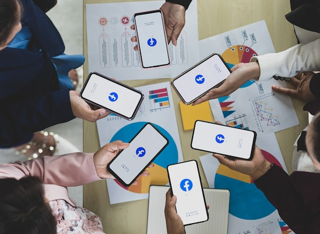 Bangkok/thailand - august 06, 2021: people hold smartphones in different brands and various operating systems with logos of facebook, the most popular social network applications.