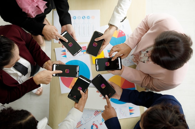 Bangkok/thailand - august 06, 2021: people hold smartphones in different brands and various operating systems with logos of instagram social applications.