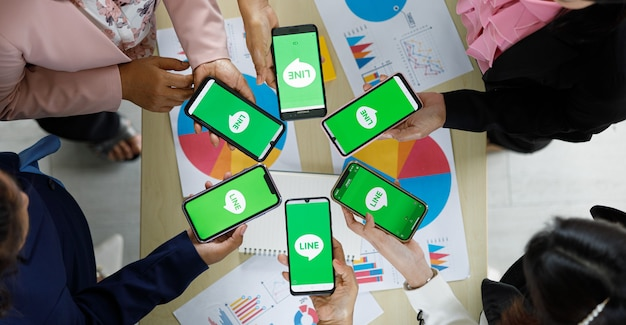 Bangkok/thailand - august 06, 2021: people hold smartphones in different brands and various operating systems with logos of line app, one of most popular messege applications.