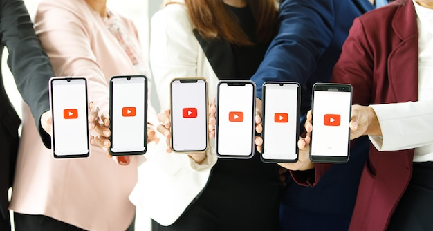 Bangkok/thailand - august 06, 2021: people hold smartphones in different brands and various operating systems with logos youtube, the most popular video portal in the world.
