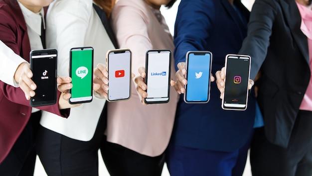 バンコク/タイ-2021年8月6日:人々は、ソーシャルアプリケーション、twitter、instagram、tiktok、linkedin、line、youtubeのさまざまなロゴが付いたさまざまなブランドやオペレーティングシステムのスマートフォンを持っています。
