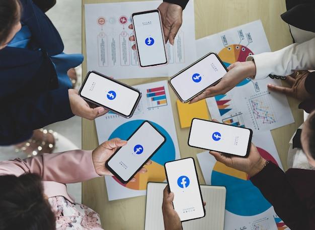 バンコク/タイ-2021年8月6日:人々は、最も人気のあるソーシャルネットワークアプリケーションであるfacebookのロゴが付いたさまざまなブランドやさまざまなオペレーティングシステムのスマートフォンを持っています。