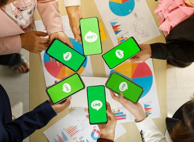 バンコク/タイ-2021年8月6日:人々は、最も人気のあるメッセージアプリケーションの1つであるlineアプリのロゴが付いた、さまざまなブランドのスマートフォンとさまざまなオペレーティングシステムを持っています。