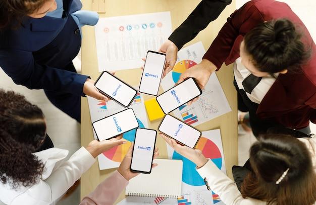 バンコク/タイ-2021年8月6日:人々は、linkedin、ソーシャルアプリケーションのロゴが付いたさまざまなブランドやさまざまなオペレーティングシステムのスマートフォンを持っています。
