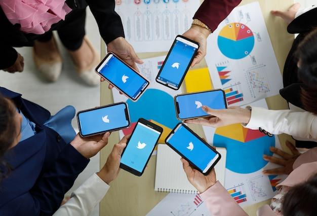 バンコク/タイ-2021年8月6日:人々は、twitterソーシャルアプリケーションのロゴが付いたさまざまなブランドやさまざまなオペレーティングシステムのスマートフォンを持っています。