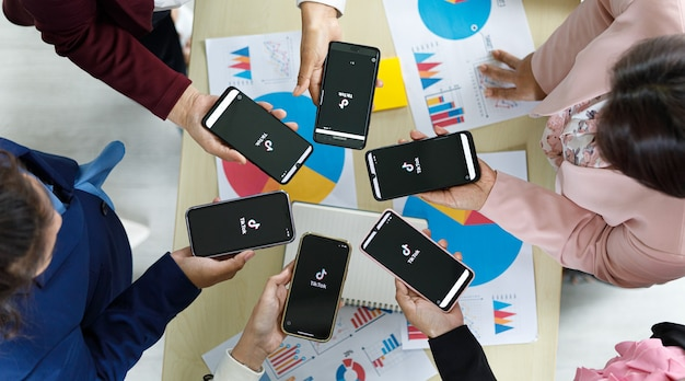 バンコク/タイ-2021年8月6日:人々は、最も人気のあるビデオソーシャルネットワークの1つであるtiktokのロゴが付いたさまざまなブランドとさまざまなオペレーティングシステムのスマートフォンを持っています。