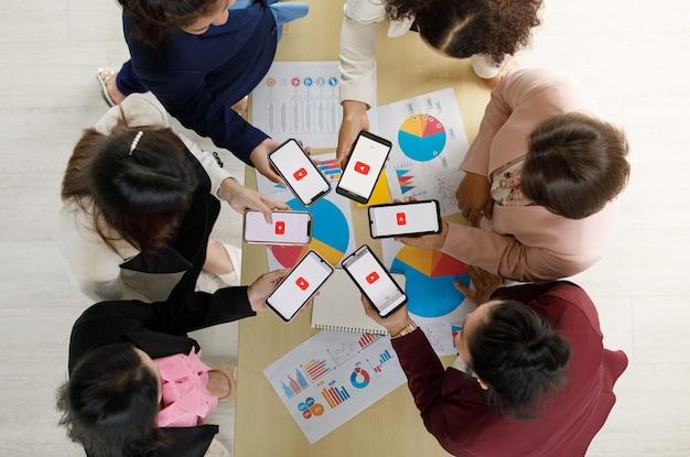 バンコク/タイ-2021年8月6日:人々は、世界で最も人気のあるビデオポータルであるyoutubeのロゴが付いたさまざまなブランドとさまざまなオペレーティングシステムのスマートフォンを持っています。