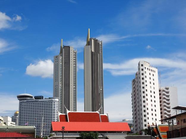 Бангкок, таиланд, вид на город с ярким ясным голубым небом, высокими зданиями и традиционной крышей храма