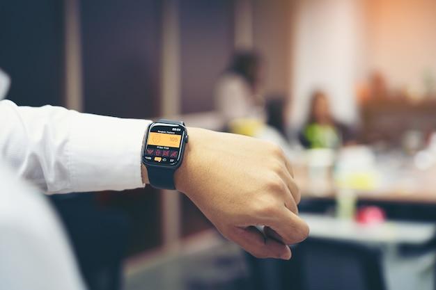 バンコクタイ王国-2019年12月19日:オフィスの画面にpm 2.5のapple watchシリーズ4を持つ男の手。 apple watchは、apple inc.によって作成および開発されました。