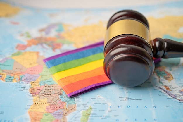 タイ、バンコク-2020年12月1日世界の地球地図上の裁判官弁護士のためのガベル付きlgbtレインボーフラッグ。
