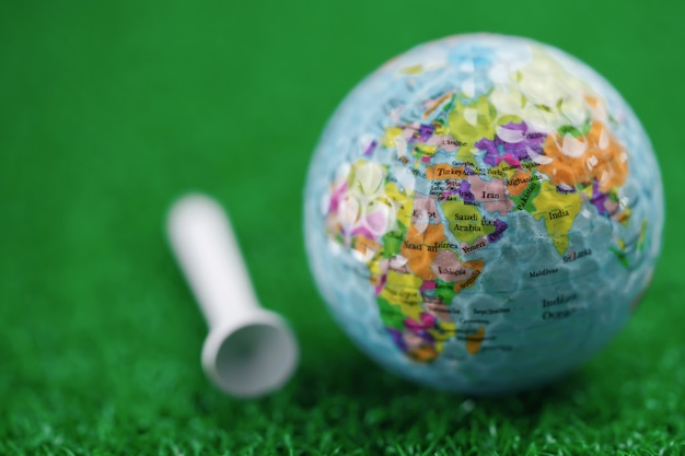 Bangkok, thailand, july 1, 2020 world globe map at golf ball with on green lawn or field.