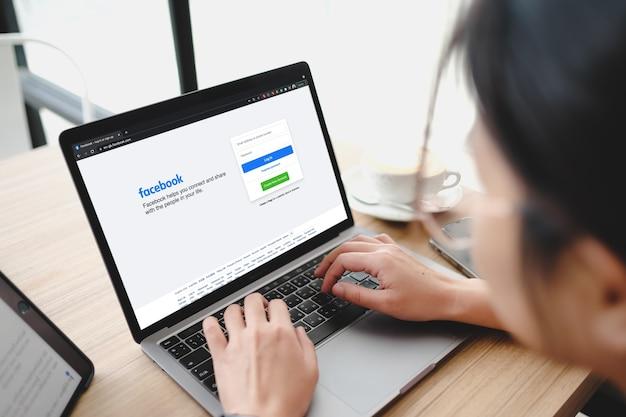Бангкок. таиланд. 1 июня 2021 г. - логотип приложения для социальных сетей facebook при входе в систему, страница регистрации для регистрации на экране приложения на портативных компьютерах в руке делового человека в кафе. Premium Фотографии
