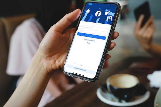 방콕. 태국. 2021년 3월 1일 로그인 시 facebook 소셜 미디어 앱 로고, 직장에서 비즈니스 사람의 손에 있는 iphone 스마트 장치의 모바일 앱 화면에서 등록 등록 페이지