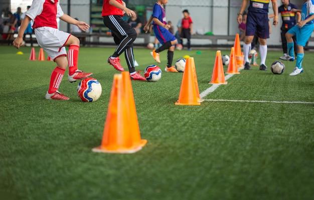 バンコク、タイ-2018年5月9日:バックグラウンドでタイをトレーニングするためのコーンと芝生のフィールドでのサッカーボールの戦術サッカーアカデミーで子供たちをトレーニングする