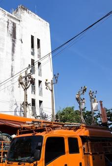 방콕/태국 - 2016년 11월 19일:방콕의 전기 기둥 전봇대에서 작업하는 많은 전기 기술자 수리 작업자