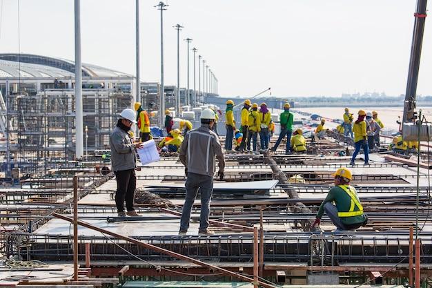 バンコク、タイ-2019年11月22日:建設業界のエンジニアの職長が立って、労働者チームが高い安全性で働くように空港に命令します