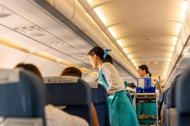 Bangkok, thailand - sep 27, 2018 - bangkok airways flight attendant serve drink to passeng