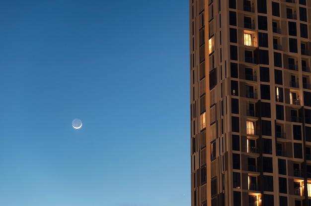 Бангкоструктура освещения кондоминиума и луна в голубом небе в центре города