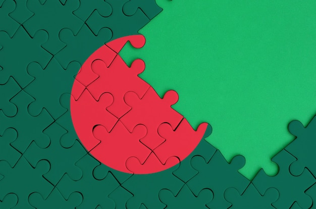 Bangladesh flag is depicted on a completed jigsaw puzzle with free green copy space on the right side